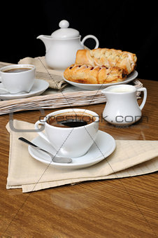 A cup of black coffee with a milkman with a tray of pastries