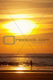 Sunset on a beach with silhouette of a kid