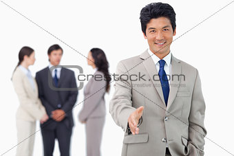 Businessman with colleagues behind him offering his hand