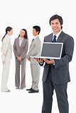 Smiling salesman showing laptop screen with team behind him