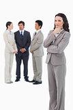 Thinking saleswoman with team behind her