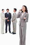 Saleswoman talking on cellphone with colleagues behind her