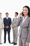 Smiling saleswoman on cellphone with team behind her