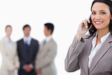 Smiling saleswoman on mobile phone with colleagues behind her