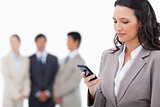 Saleswoman writing text message with colleagues behind her