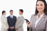 Smiling saleswoman holding cellphone with team behind her