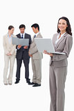 Smiling saleswoman with laptop and associates behind her