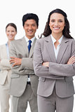 Smiling businesswoman with team and folded arms