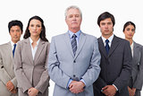 Mature businessman standing with his colleagues