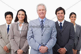 Smiling mature businessman standing with team