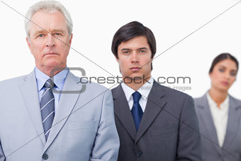 Mature salesman standing with employees