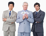 Senior businessman with money standing between his employees