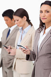 Businesswoman with cellphone next to colleagues