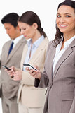 Smiling businesswoman with cellphone next to colleagues