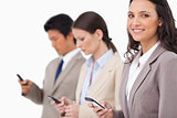 Smiling saleswoman with cellphone next to colleagues