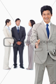 Businessman with colleagues behind him extending his hand
