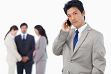 Serious businessman on cellphone with team behind him