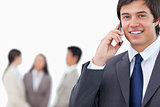 Smiling salesman on his cellphone with team behind him