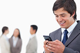 Salesman writing text message with team behind him
