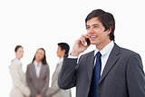 Salesman talking on cellphone with colleagues behind him