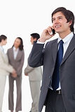 Salesman talking on mobile phone with team behind him