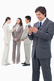 Smiling salesman holding mobile phone with team behind him