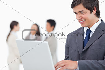 Salesman with laptop and colleagues behind him