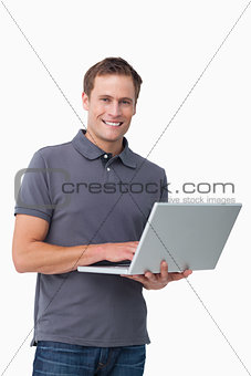 Smiling young man with his laptop