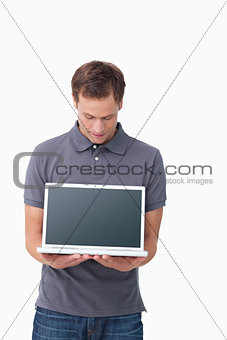 Young man showing screen of his notebook