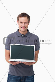 Smiling young man showing screen of his notebook