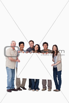 Smiling group of friends holding blank sign together