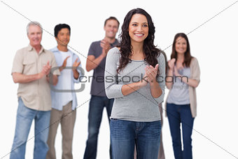 Clapping young woman with friends behind her