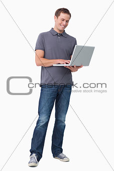 Smiling young man working on his laptop