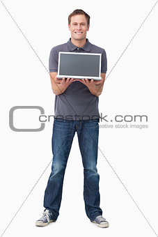 Smiling young man showing his laptop screen