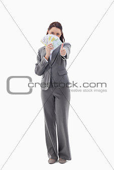 Businesswoman approving and hiding with bank notes in her hand