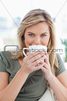 Close up, woman with a mug held up in front of her mouth and loo