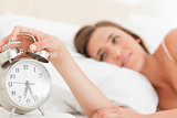 Woman silencing her alarm clock, focus on the clock