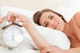 Woman looking forward as she silences her alarm clock