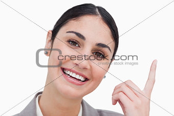 Close up of smiling businesswoman pointing up