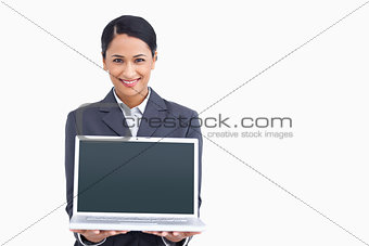 Close up of smiling saleswoman presenting laptop screen