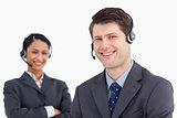 Close up of smiling male call center agent with colleague behind