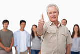 Mature man giving thumb up with young people behind him