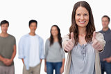 Smiling woman with friends behind her giving thumbs up