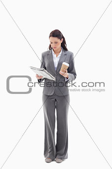 Businesswoman with a coffee reading a newspaper