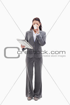 Businesswoman drinking a coffee and reading a newspaper