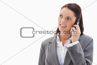 Close up of a businesswoman looking up while smiling on the phon