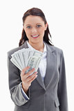 Close-up of a businesswoman smiling and holding a lot of dollar