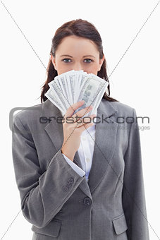 Businesswoman hiding behind a lot of dollar bank notes