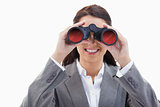 Businesswoman smiling and looking through binoculars