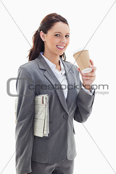 Businesswoman smiling with a newspaper drinking a coffee